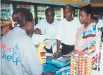 A Cashier in a Mobil Service Station On The Run convenience store explaining the voucher redemption process to Dr Awa Coll-Seck, Executive Director of Roll Back Malaria. http://www.ipieca.org/sites/default/files/system/insecticide.pdf