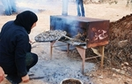 A local Palestinian woman prepares taboun bread for visitors in a traditional wood-burning oven, http://imeu.net/news/article0014939.shtml
